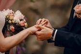 Novio poniendo anillo en la ceremonia a su novia