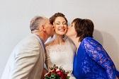 Novia feliz recibiendo un beso como felicitación de su boda